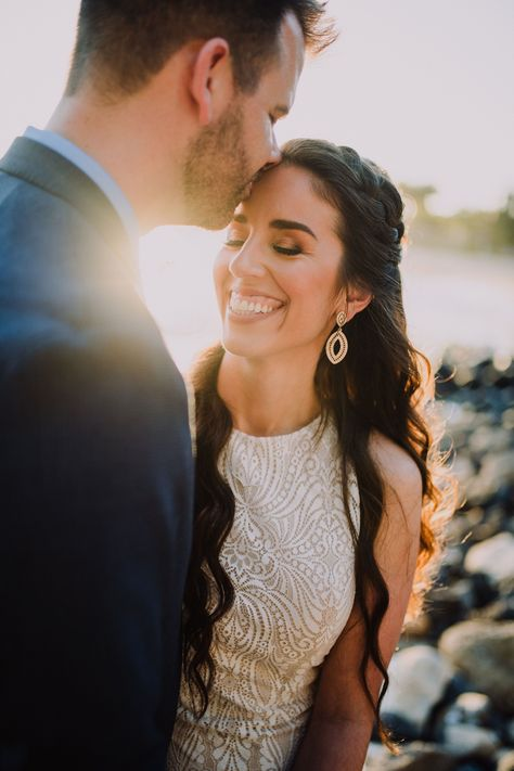 One look at our blushing Bride and you can tell how magical this day was! This modern elopement took place on the stunning beaches of Hawaii. An incredible sunset created the perfect canvas for these amazing photographs of the ceremony.