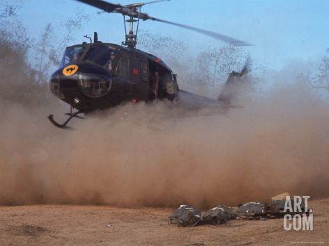 February American Huey helicopter touching down in a cloud of dust to retrieve bodies of soldiers killed in a recent firefight during the Vietnam War.