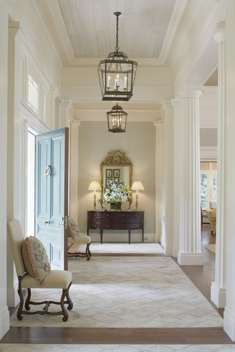 beautiful foyer....tile mixed with wood flooring, white washed wood plank ceiling accent, mouldings, columns, lanterns...