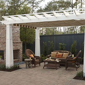 This unique patio includes a pergola with a retractable canopy of outdoor fabric that is great for protection from sun and rain. Comfy seating is centered around a fireplace and creates an outdoor living area that is great for parties and entertaining.Tour the Bayou Bend Idea House