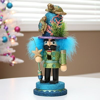 A traditional Christmas nutcracker displays an unconventional, nature-inspired hat. Adorned with beloved symbols of nature, he peeks out gleefully from under his embellished hat. Perfect as a gift or  purchase to display in your home this season! Measures 11'h.