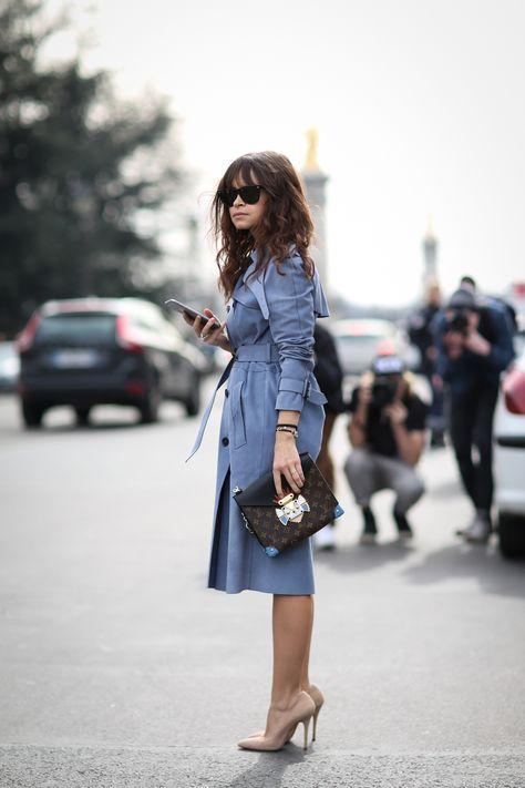 slfmag: Fashion week street style fashion: Miroslava Duma in royal blue trench coat holding Louis Vuitton clutch bag + nude pumps.