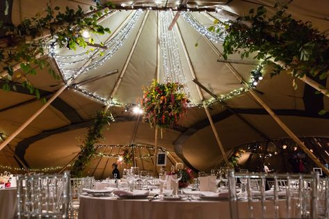 Hanging floral chandelier and fairy lights for a rustic tipi wedding Image by James Darling Photography.  #tipiwedding #rusticwedding #weddingideas #bohemianwedding #bohemianbride  #rustictipiwedding #outdoorwedding