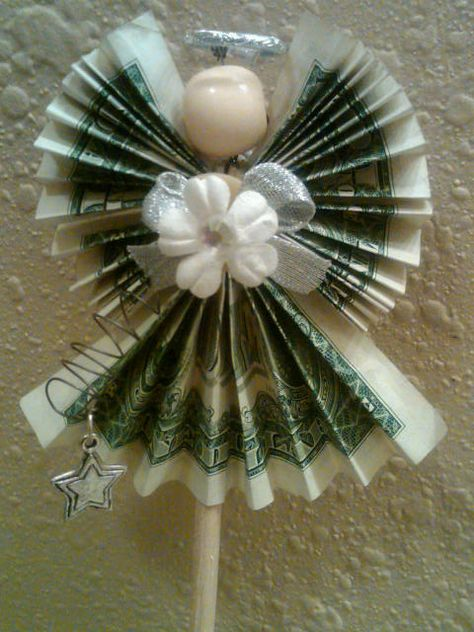 Origami Angel made with 3 one dollar bills. Each wing is a dollar and the gown is one dollar. The flower and bow are glued to a button. The button is attached to the wire that holds the dollars together as well has the bead head and halo. The halo is a decorative wedding band
