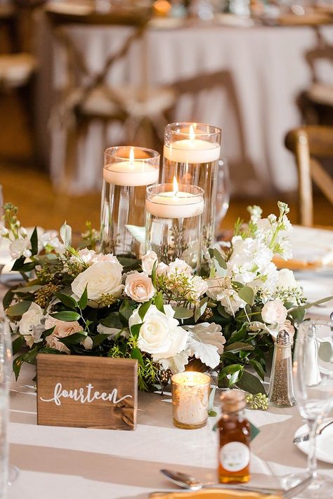 Wedding Table Decorations 325455510574710570 - Rustic Elegant Wedding Reception Decor, White, Blush Pink, Ivory and Greenery Centerpiece with Tall Glass Cylinder Floating Candles and Wooden Table Number Sign Source by Greenery Centerpiece, Candle Wedding Centerpieces, Floral Centerpieces, Centerpiece Ideas, Floating Candles Wedding, Wedding Reception Table Decorations, Rustic Wedding Reception, Wedding Flower Decorations, Wedding Table Signs