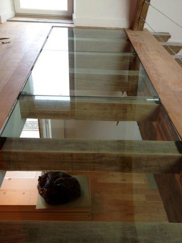 """En face de l'escalier qui relie les deux étages, Jean-Baptiste Guigon a imaginé et installé un sol en verre transparent. """"Cela permet d'apporter de la lumière au séjour, situé en dessous"""" explique-t-il.(rénovation Manoir XVIIIème)"""