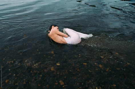 A woman in a dress lays in the flow of a river and lets peace wrap around her body.  #peaceful #nature #water #stockphoto #stocksy