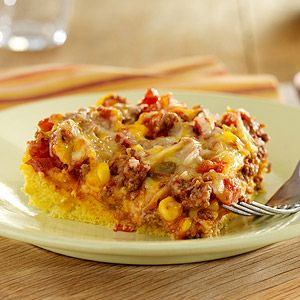 Cornbread base topped with beef, zesty tomatoes, corn, and cheese for a flavorful baked entree.