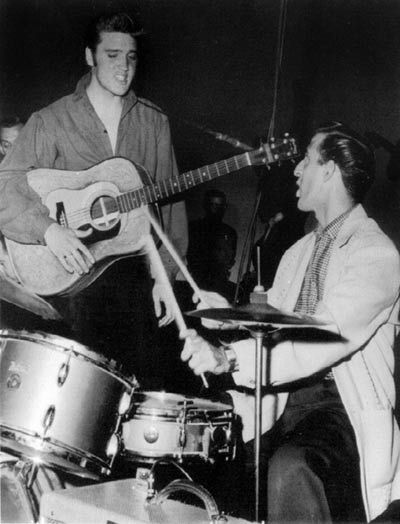 DJ Fontana was staff drummer for the Louisiana Hayride. Country Music had no place for drums in those days- not visible drums at least, and DJ played behind the stage curtain. The first time he played with Elvis and the Blue Moon Boys was on October 16, 1954. He played behind the curtain as usual, but after that date he played out in front with the rest of the band, and joined Elvis' group full-time in August of 1955.