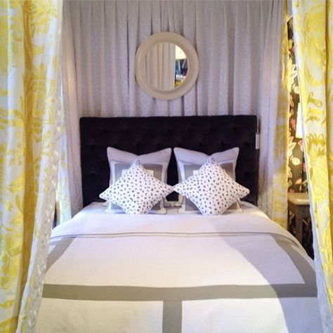 Thibault put together a perfectly dressed bed with their tufted dark blue upholstered headboard, white and dove gray bedding and sunny yellow patterned drapery. Thibault, Market Square, 3rd Floor.