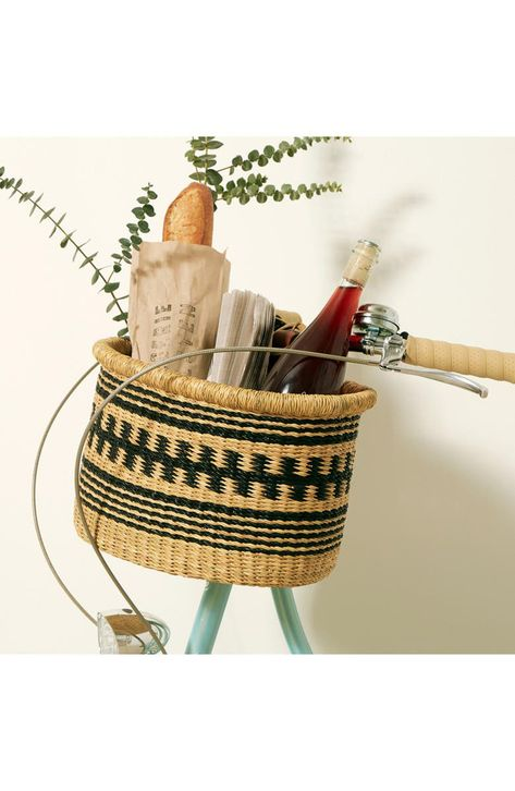 Handwoven by Ghanaian artisans, this bicycle basket is shaped from locally sourced vetiver grass and features a varied two-tone pattern.