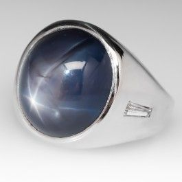 This incredible mens star sapphire ring is heavy and substantial just like a mens ring should be. The ring features a natural untreated 17 carat sapphire with an awesome star. The ring is nicely accented with high quality tapered baguette diamonds grading F in color and VVS in clarity. The sapphire features a medium dark blue tone with slightly grayish saturation and has a strong, centered, complete 6-ray star with very good movement. This is an awesome mens ring and it is in fantastic condit...