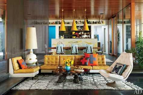 Ball-chain curtains define the sunken living area, where Adler grouped a sofa, slipper chair, table lamp, and throw pillows, all of his own design; the cocktail table, Geoffrey Harcourt shell seat, and Beni Ourain rug are vintage.