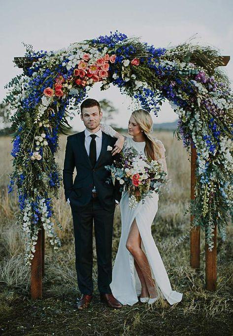 Modern bride and groom standing under big and lush floral arch. @myweddingdotcom