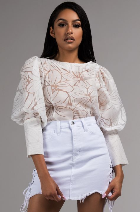 Just like a warm summer night, there's nothing else quite like this delicately detailed blouse. The AKIRA Label Warm Nights Puff Sleeve Blouse has a structured fit with a wide bateau neckline, puff sleeve arm with stiff oxford button cuffs, and a back but