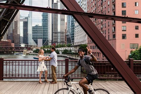 Candid Chicago engagement photo with bicyclist at Kinzie Bridge