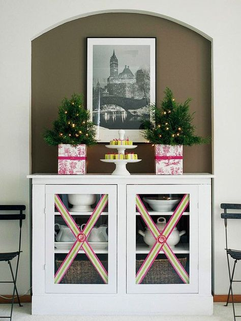 Dress cabinet doors and windows with a flourish of ribbon -- a useful, inexpensive Christmas decorating trim to keep on hand! http://www.bhg.com/christmas/crafts/low-cost-christmas-projects/?socsrc=bhgpin121314easyribboncabinetflourish&page=21