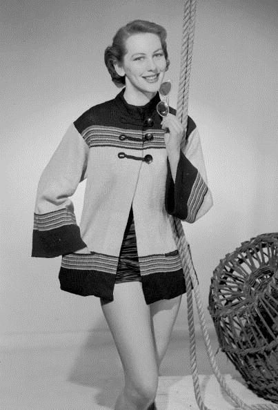Model wearing a short knitted beach coat with toggle fastening and bell shaped sleeves, February 1955.