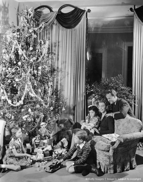 1950s: Family gathered around Christmas tree with gifts.