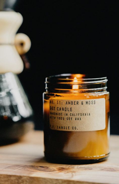 A candle hand-poured into an apothecary-inspired amber glass jars with a signature label and a brass lid.