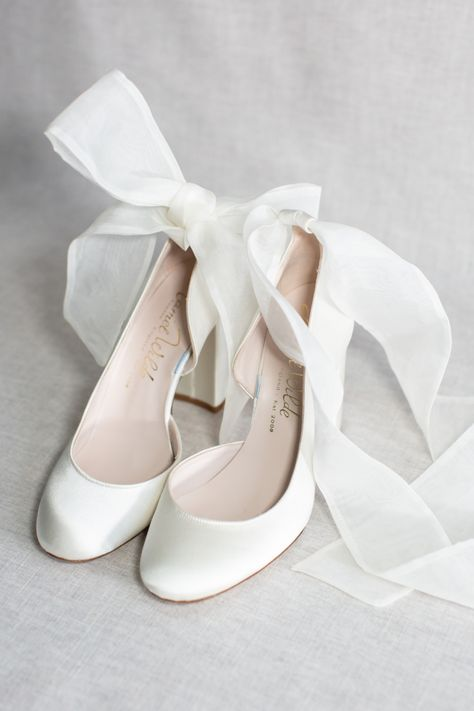 A striking block heel bridal court shoe handcrafted in luxury ivory satin the shoe is finished with a beautiful ankle tie in gauzy organza ribbon for added style. We absolutely adore these ivory wedding shoes, they're elegant and comfortable with the block heel. This style comes with an optional wide satin ankle strap, too. Wedding heels with bows are such a feminine and romantic choice. #weddingshoes #bridalshoes #weddingheels