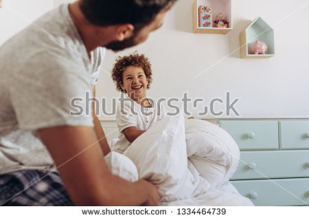 Stock Photo Father And Son Having A Pillow Fight Sitting On Bed