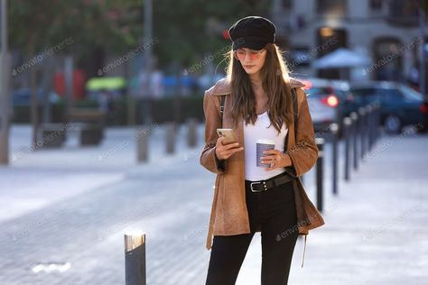 Pretty young woman using her mobile phone while holding a coffee and standing in the street. By nenetus¡¯s photos #Ad , #AD, #woman, #mobile, #Pretty, #young