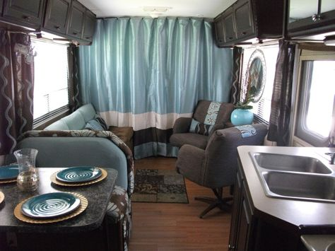 """DIY Glam RV Remodel with Tufted Wall, Updated our 25 year old RV from mauve """"pink"""" color scheme to a more appealing brown and aqua/blue interior, featuring my DIY tufted wall in the bedroom and other glam, romantic accents., Living area---Deep chocolate browns and aqua/blue decor carries over into the living area.  The mauve """"pink"""" carpet is replaced with inexpensive laminate flooring.  The pumpkin stained cabinets got a dark brown coat of paint and new pulls.  The driving cabin has also receive"""