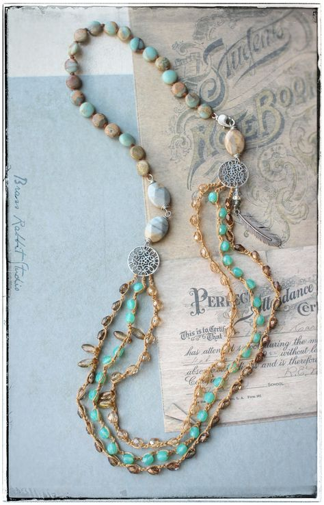 """Triple strand Bohemian crochet and knotted necklace with hand made silver filigree connectors and feather charm, ocean jasper, serpentine, and three strands of crochet Czech glass crystals. Measures approximately 30"""""""
