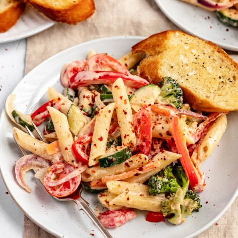 Delicious vegan pasta primavera packed with tender vegetables and tossed in a creamy garlic cashew sauce. This easy vegan pasta primavera recipe has wonderful flavors and plenty of protein and healthy fats for a comforting plant-based meal the whole family will love! #vegan #vegandinner #plantbased #vegetarian #dinner #healthylunch #dairyfree #glutenfree #zucchinirecipe
