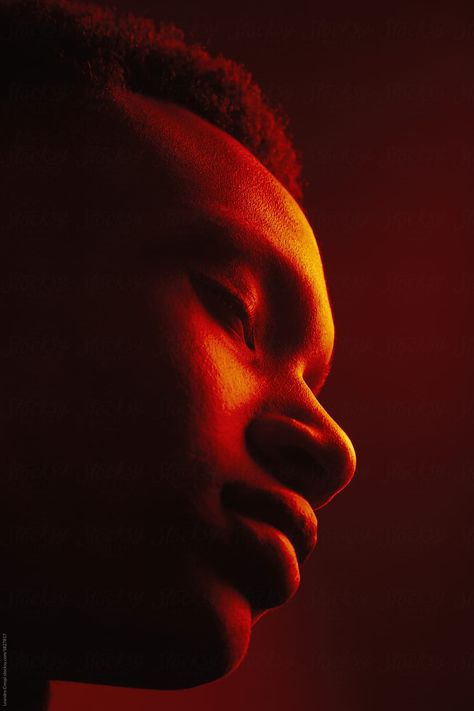 African American man portrait under red lights  by Leandro Crespi for Stocksy United