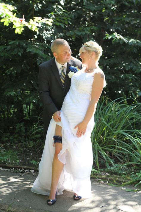 Gorgeous bride with her new husband showing off her wedding garter. This was a custom made design. Navy blue organza, swarovski crystals with military colour hand tied bows. Any if the accessories on my site can be custom made in any colour of your choice. I also make dolly bags & wedding ring cushions. #weddingaccessories #bridal #weddingdesign #onlineshop #bridalgown #engagement #weddingphoto