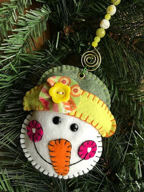 Wool blend felt snow girl ornament/hanger. Ornament has been blanket stitched by hand in coordinating colors. Hat colors in green and gold. Accented with heart brad cheeks and black brad eyes with flower button on hat. Embroidered mouth. Hung from beaded hanger. Glass beads on brass