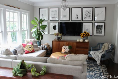 Beautiful gallery wall helps the tv blend into the background and I love all the black and white photography kellyelko.com #gallerywall #blackandwhite #photography #minted #tvgallerywall #familyroomdecor #eclecticdecor #sectionalsofa #houseplants #cozydecor #colorfuldecor
