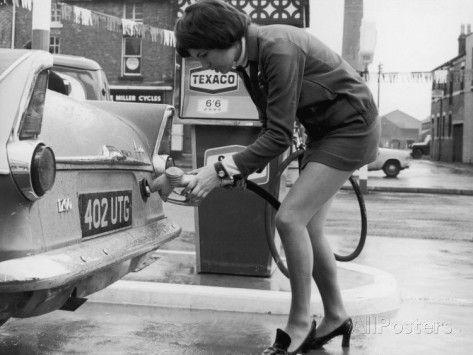 The Modern Female Petrol Pump Operator Refuelling a Car in Her Mini Skirt Photographic Print