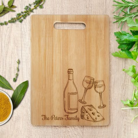 Whether in the kitchen slicing and dicing or presenting your latest charcuterie, this Laser Engraved Bamboo Wood Cutting Board with Handle is the perfect essential to have on hand. The solid bamboo wood cutting board features a beautiful grain look, highlighted with a laser engraved design of wine and cheese pairings, and comes with a handled end to easily carry wherever it's needed. Engrave with your favorite saying, a family name and date, or motto to live by. Note: This item receives laser en Large Cutting Board, Engraved Cutting Board, Personalized Cutting Board, Wood Cutting Boards, Wood Laser Ideas, Wood Laser Engraving, Decoration, Wood Burn Designs, Laser Engraved Gifts