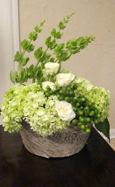 Green Hydrangeas, Bells of Ireland, Hypericum and spray roses in birch planter