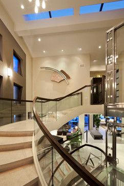 A grand foyer highlighted by a custom glass elevator and sweeping circular staircase.