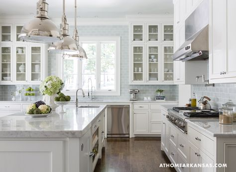 Blue-grey subway tiles by Waterworks add a subtle pop of color to the kitchen's clean lines and soft palette.