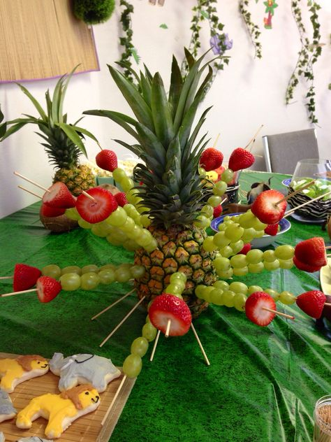 Green grape and strawberry skewers stuck in a pineapple for jungle party fruit snacks! (Tip: use craft dowels instead of skewers and use half pieces to make tripod legs on the bottom to balance it)