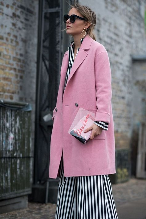Rebecca Laurey wearing a pink coat on top of a striped silk suit for the By Malene Birger show in Copenhagen, during fashion week.