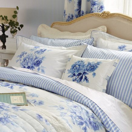 cottage blue and white bedroom with lots of cushions / pillows and floral bedspread