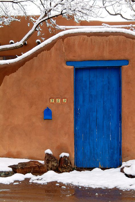 I love everything about this.  I love that such a light snow is so beautiful.  I love the warm brown stucco and the bold blue accents.  Maybe I should do something bold like this with one of my walls...