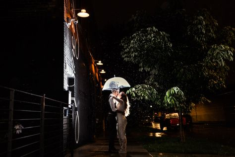 Romantic wedding photo of bride and groom outside The Joinery Chicago with umbrella in the rain