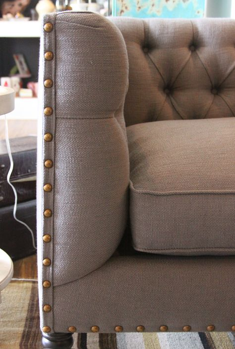 gray linen sofa with brass nail head detail
