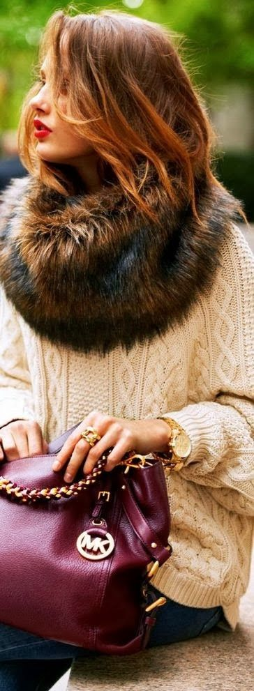 A faux fur scarf and a burgundy bag help dress up your classic oversized knit sweater