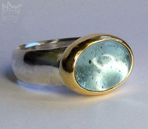 Ein traumschöner, wasserblauer Edeltopas aus Afrika, in 750er Gold gefasst, sitzt auf einer Ringschiene aus 935er Silber.