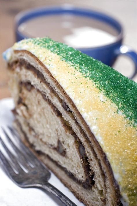 A slice of king cake  is topped with the colors of Mardi Gras.A slice of king cake  is topped with the colors of Mardi Gras.