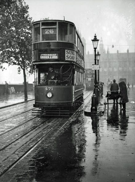 Victoria Embankment on a very wet day in 1931. The No.26 tram is making its way to Blackfriars Bridge and then Southwark Street near London Bridge. It had started its journey at Kew Bridge then along Chiswick High Road, Hammersmith Broadway then over Putney Bridge, Wandsworth High Street, Clapham Junction, Wandsworth Road, Vauxhall Station, Albert Embankment and Westminster Bridge. This route crossed the Thames three times on its way from Kew to London Bridge. Interesting to see the pedestri...