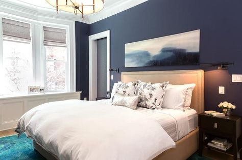 Navy and beige bedroom features walls painted navy blue lined with a beige nailhead bed dressed in ...